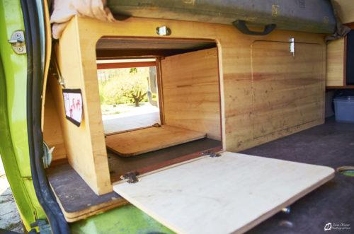 Vue depuis la porte latérale: Le caisson avec les trappes ouvertes et le tiroir à droite sous la banquette